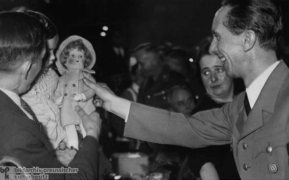 Joseph Goebbels Gives a Present to a Child during a Winter Relief Organization Event (December 1, 1936)